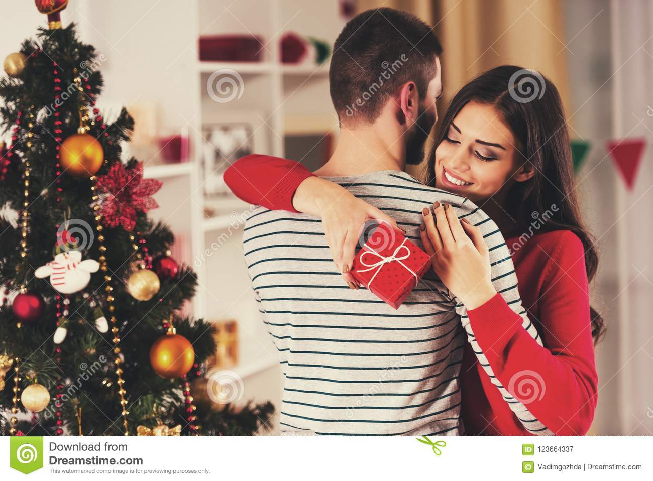 girl with red gift hugging boyfriend