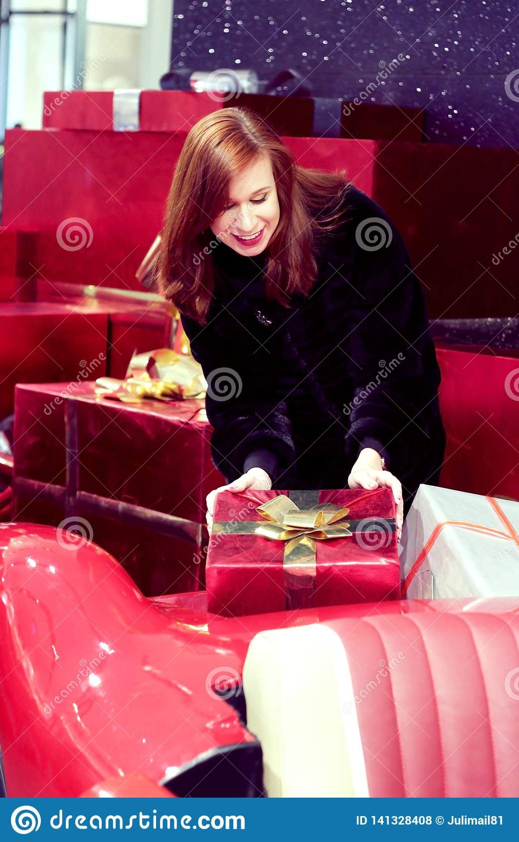 A girl with red hair is holding a box with a gift, which lies on a red car. The concept of festive mood and nice gifts