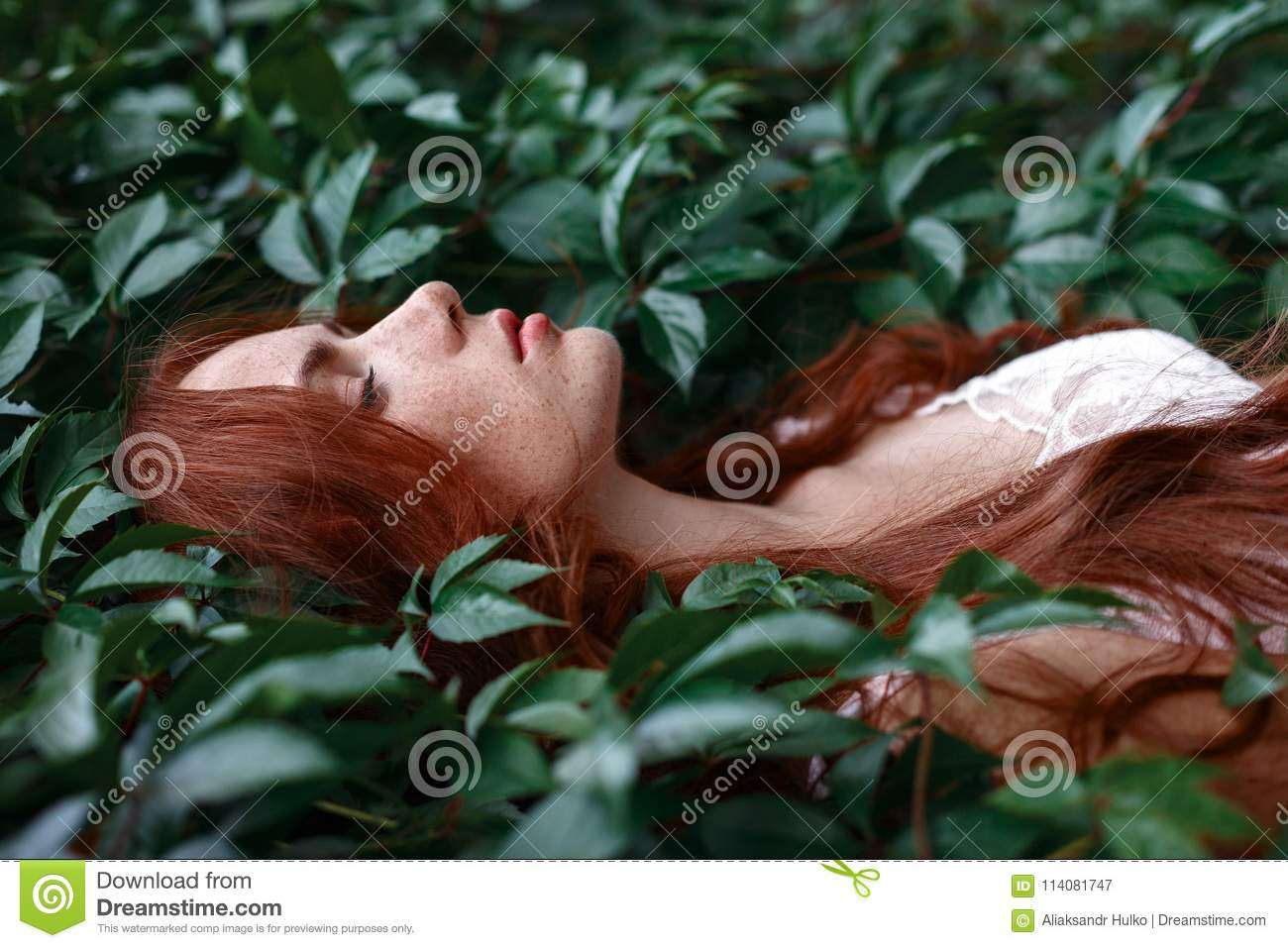 The girl with the red hair lies among the green leaves