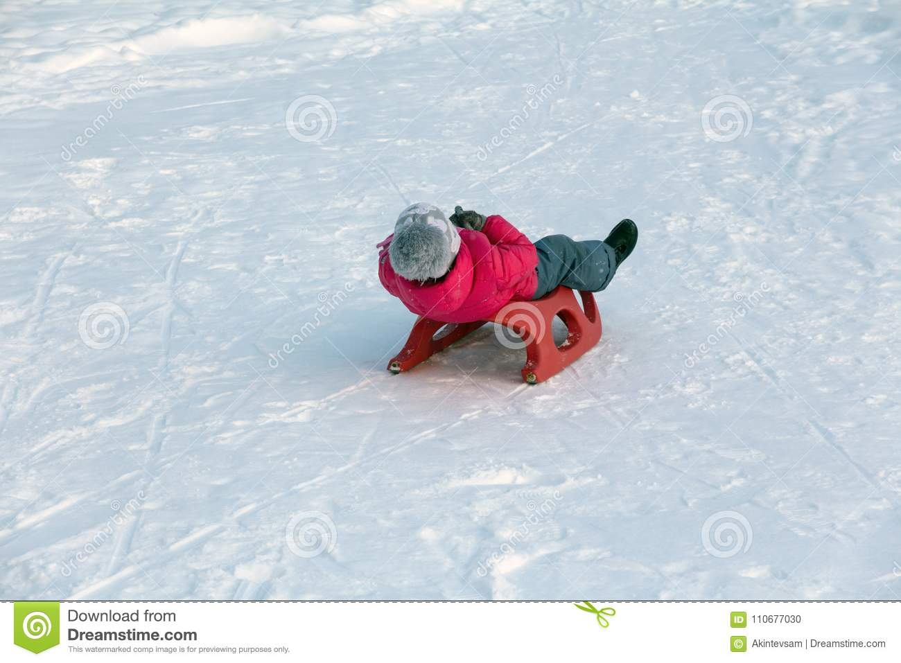 Girl in a red jacket rides off a snow slide