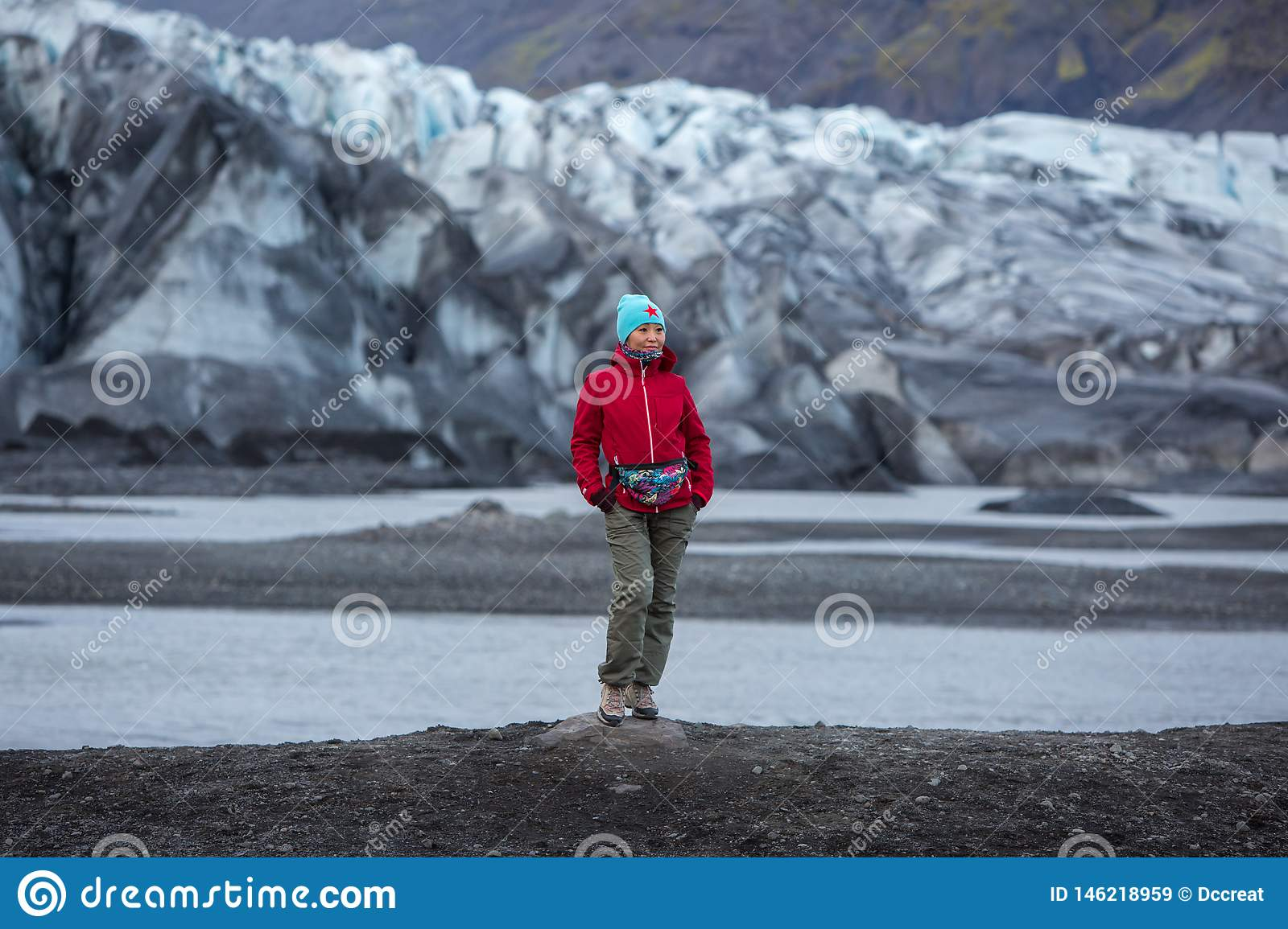 Girl in a red jacket stands on the background of a glacier