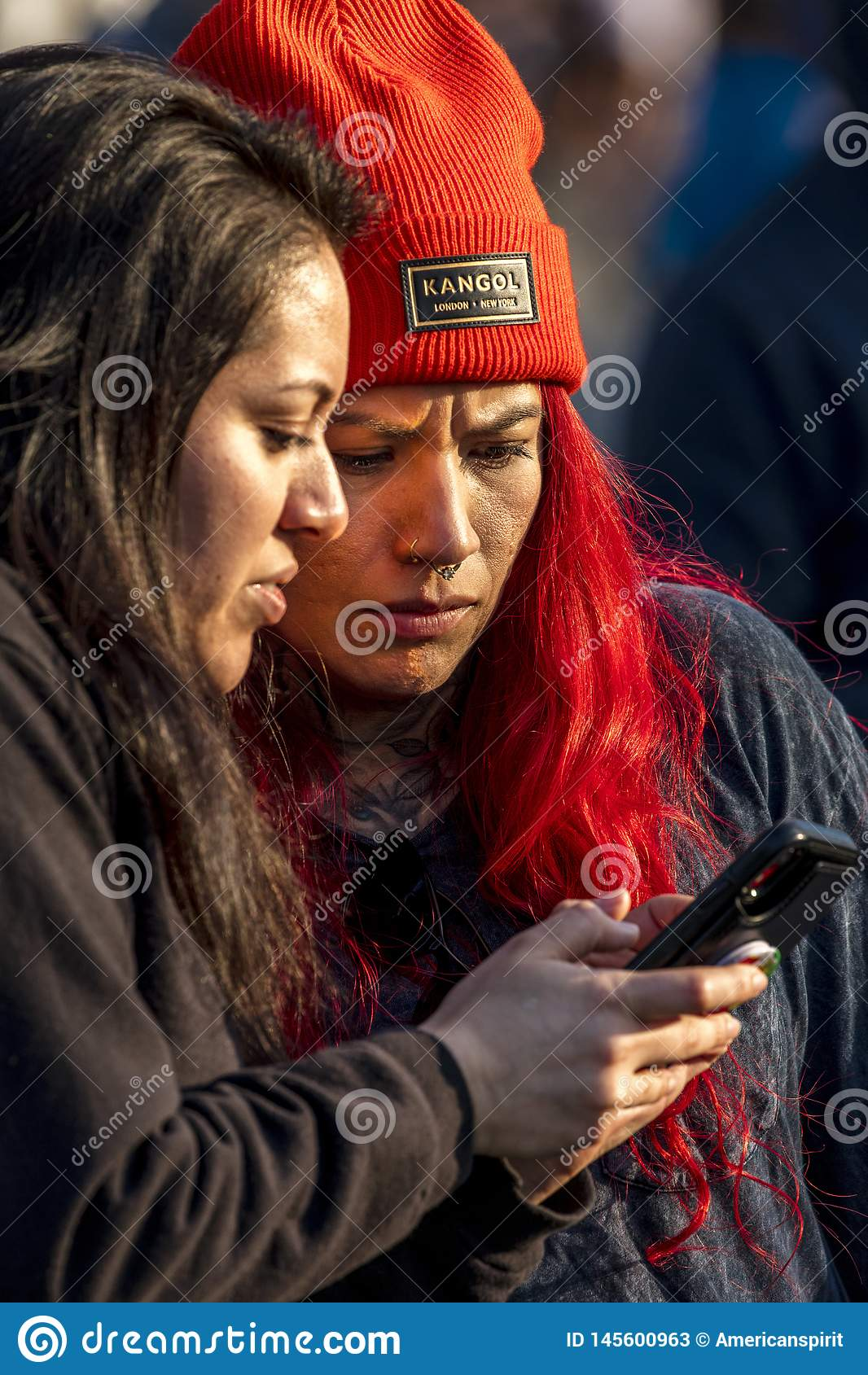 Girl with red Kangol Beany and friend looks at Cell Phone California