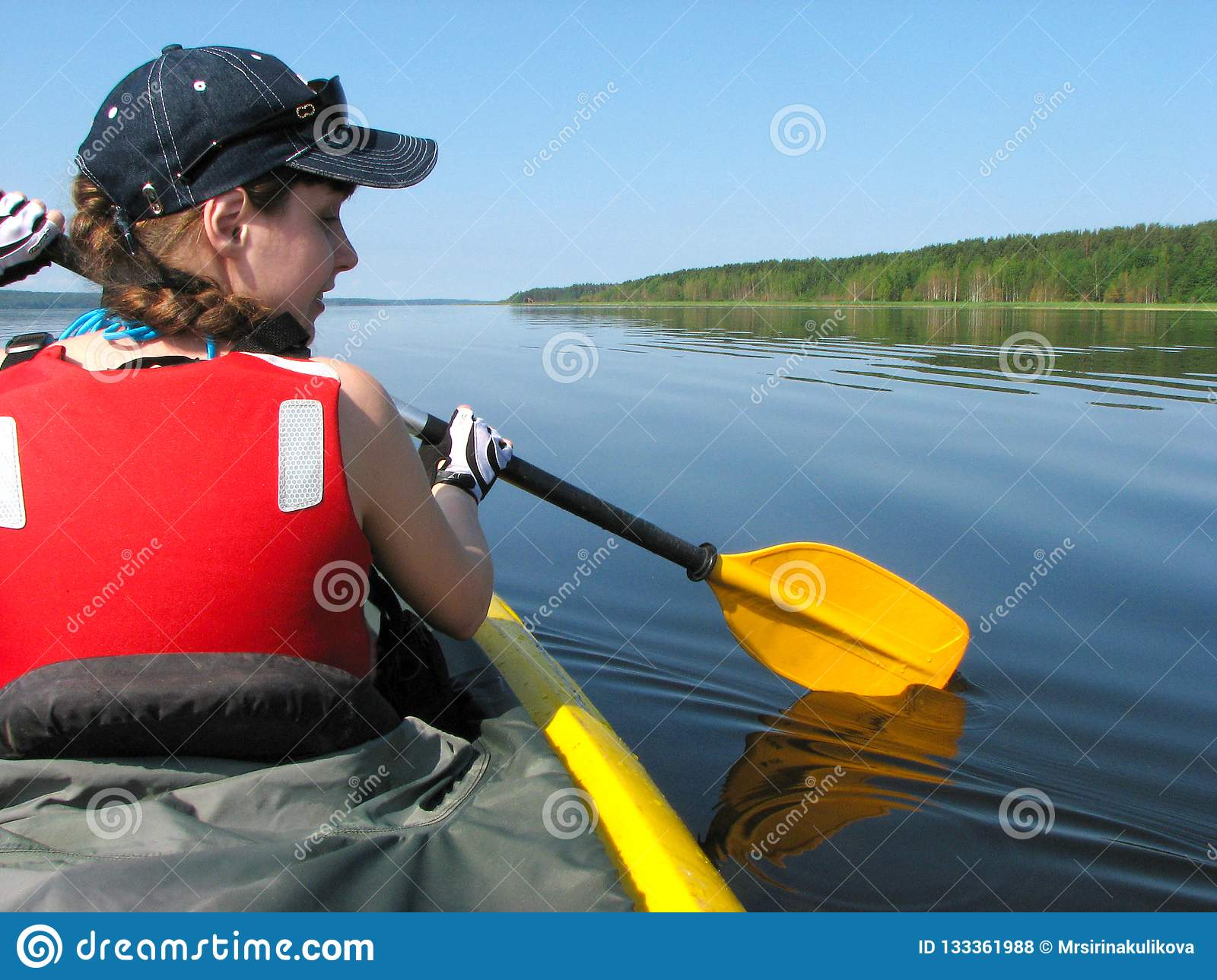 Girl in a red life jacket rows in a kayak on a lake on a sunny s