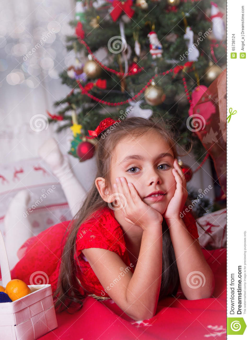 Girl in red lying under Christmas tree