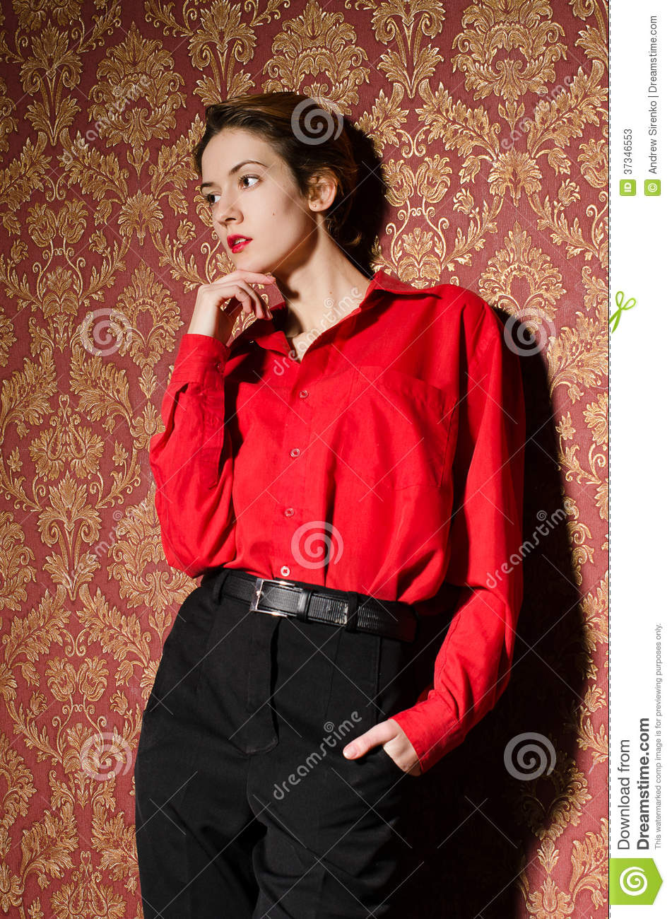 Girl in red male shirt. In retro interior