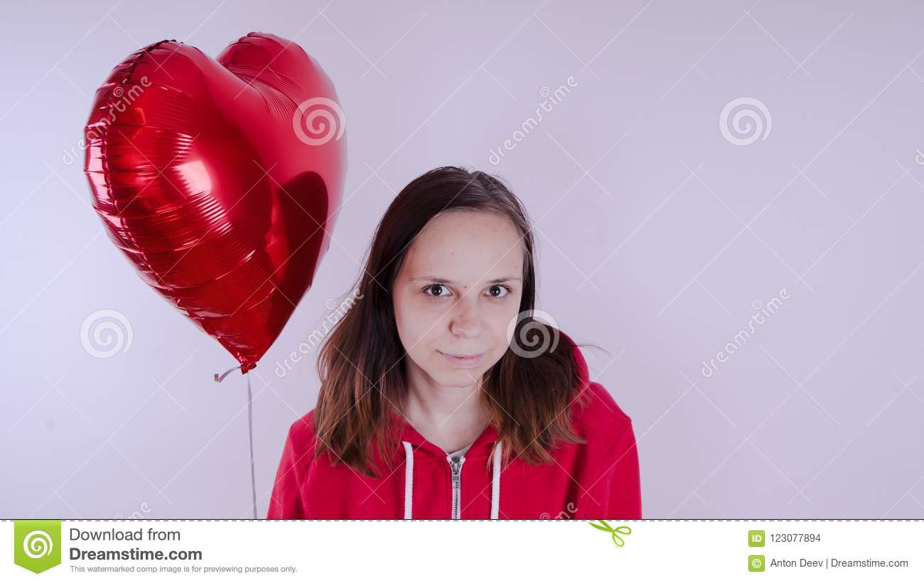 A girl in a red sweatshirt in her hand a red balloon in the form of a heart. Student posing on white background