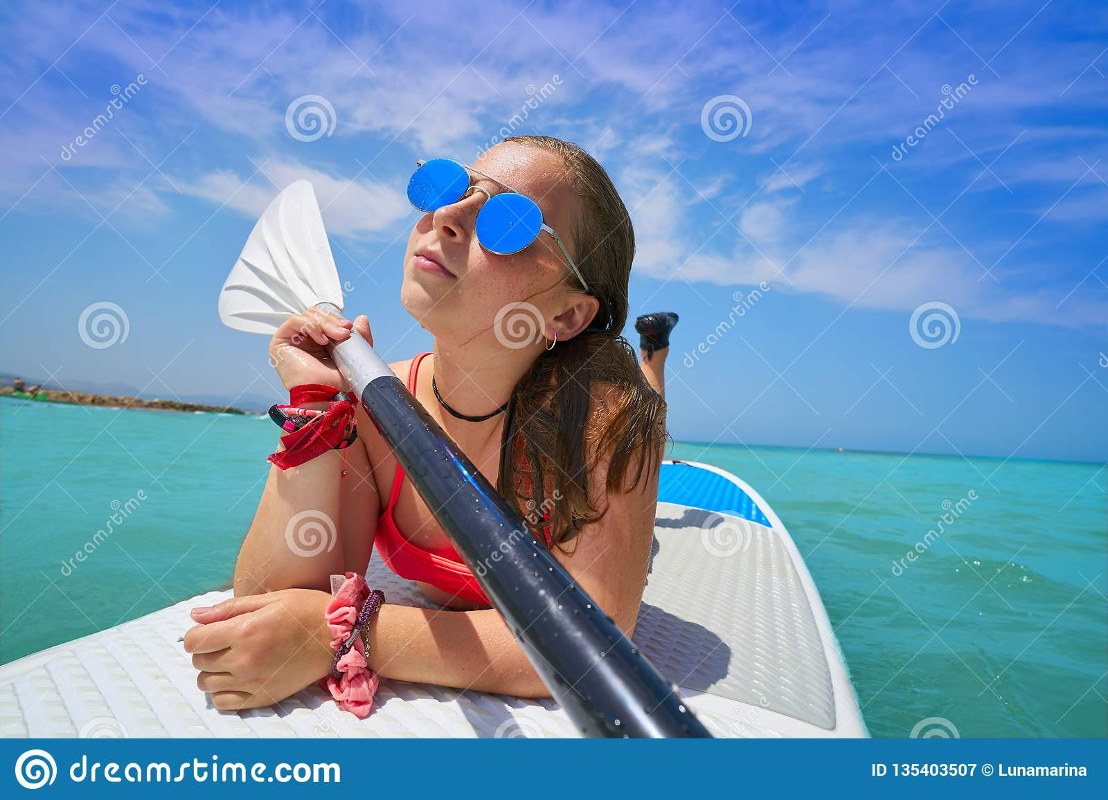 Girl relaxed lying on paddle surf board SUP