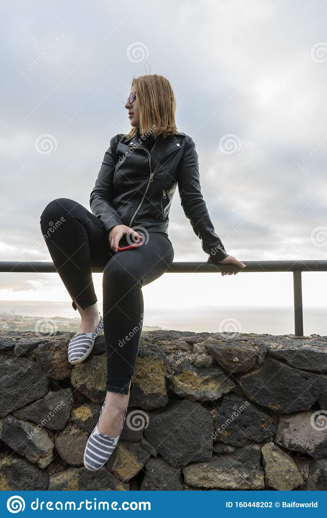 Girl Relaxing Sitting In Fence On A Viewpoint And Cell Phone In Her Legs Curvy Teen Sit In Hilltop In Silence And Serenity Stock Photo Image Of Casual Legs 160448202