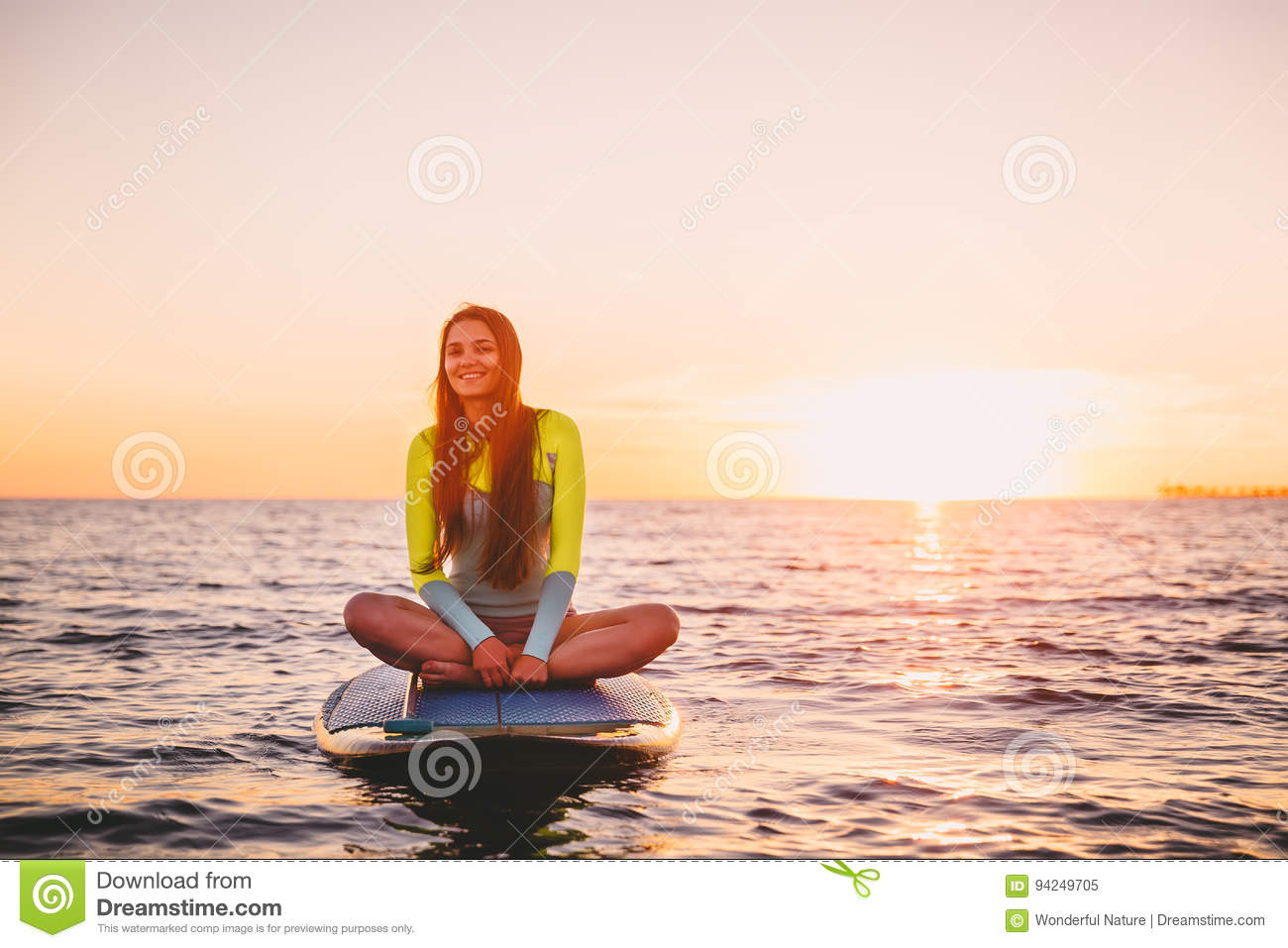 Girl relaxing on stand up paddle board, on a quiet sea with warm sunset colors.