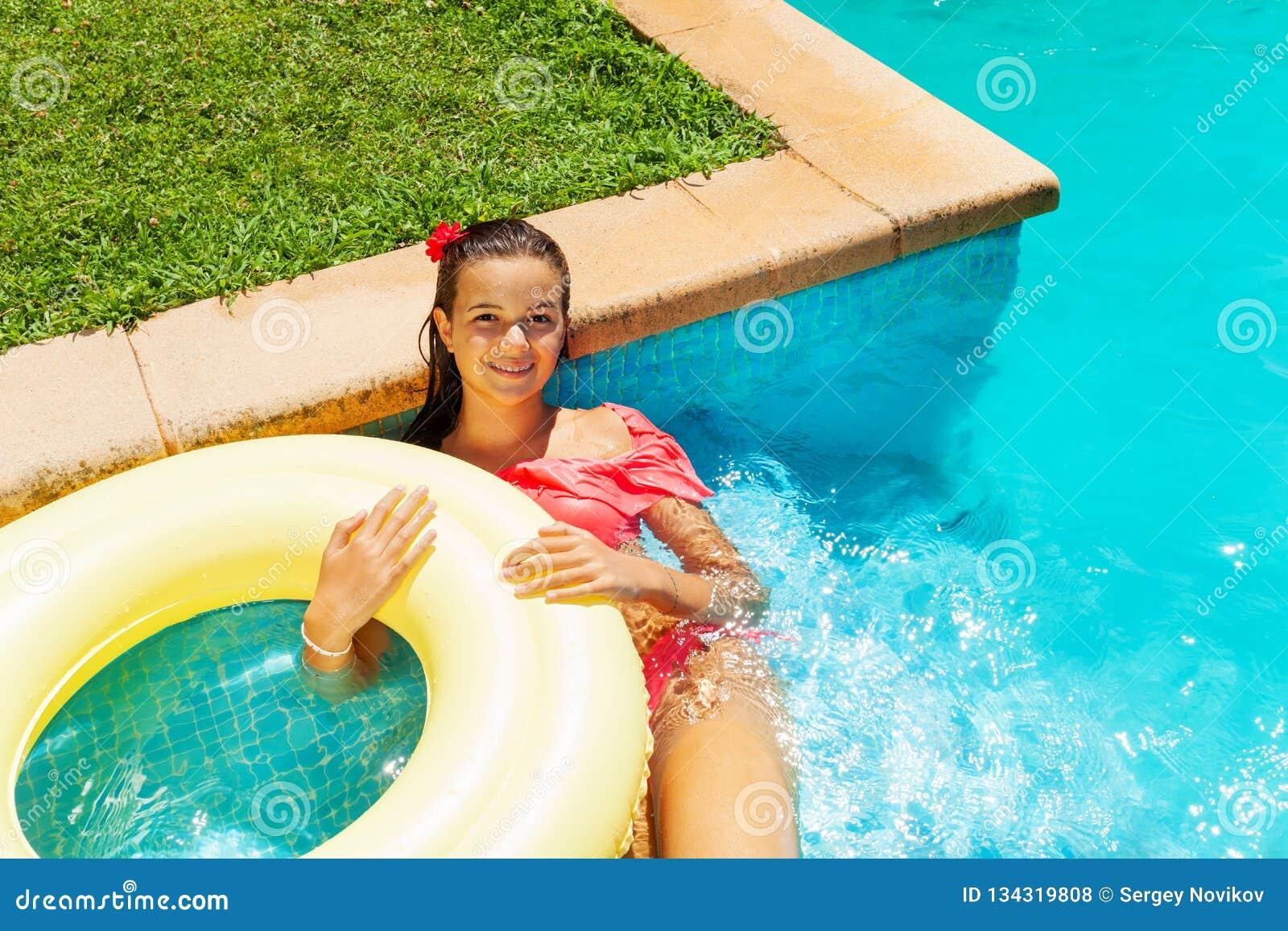 9e2a902ac57c9 Above view of teenage girl in bikini relaxing in swimming pool with big  yellow swim ring