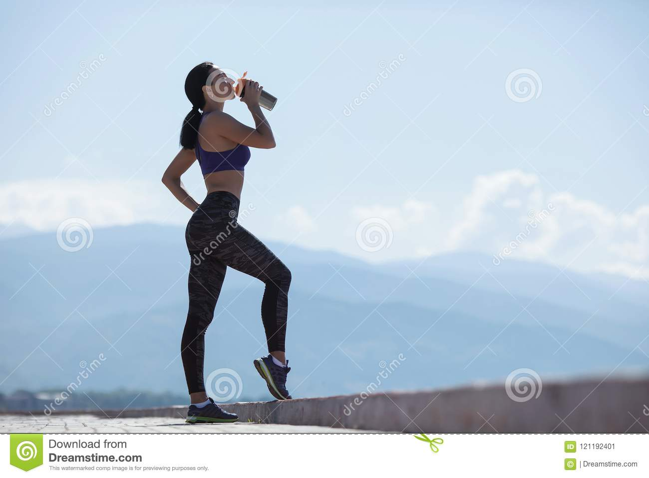 Girl resting after exercising, drink water from bottles