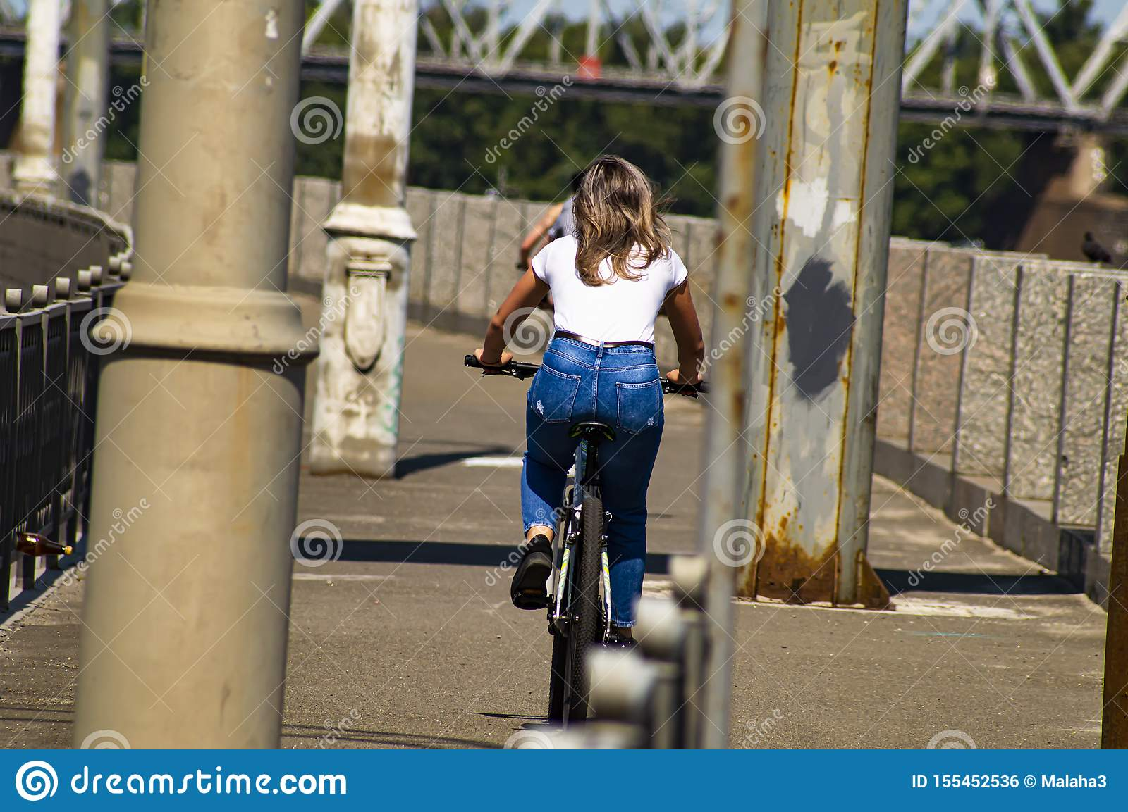Girl rides a bicycle. Back view. Sports and recreation