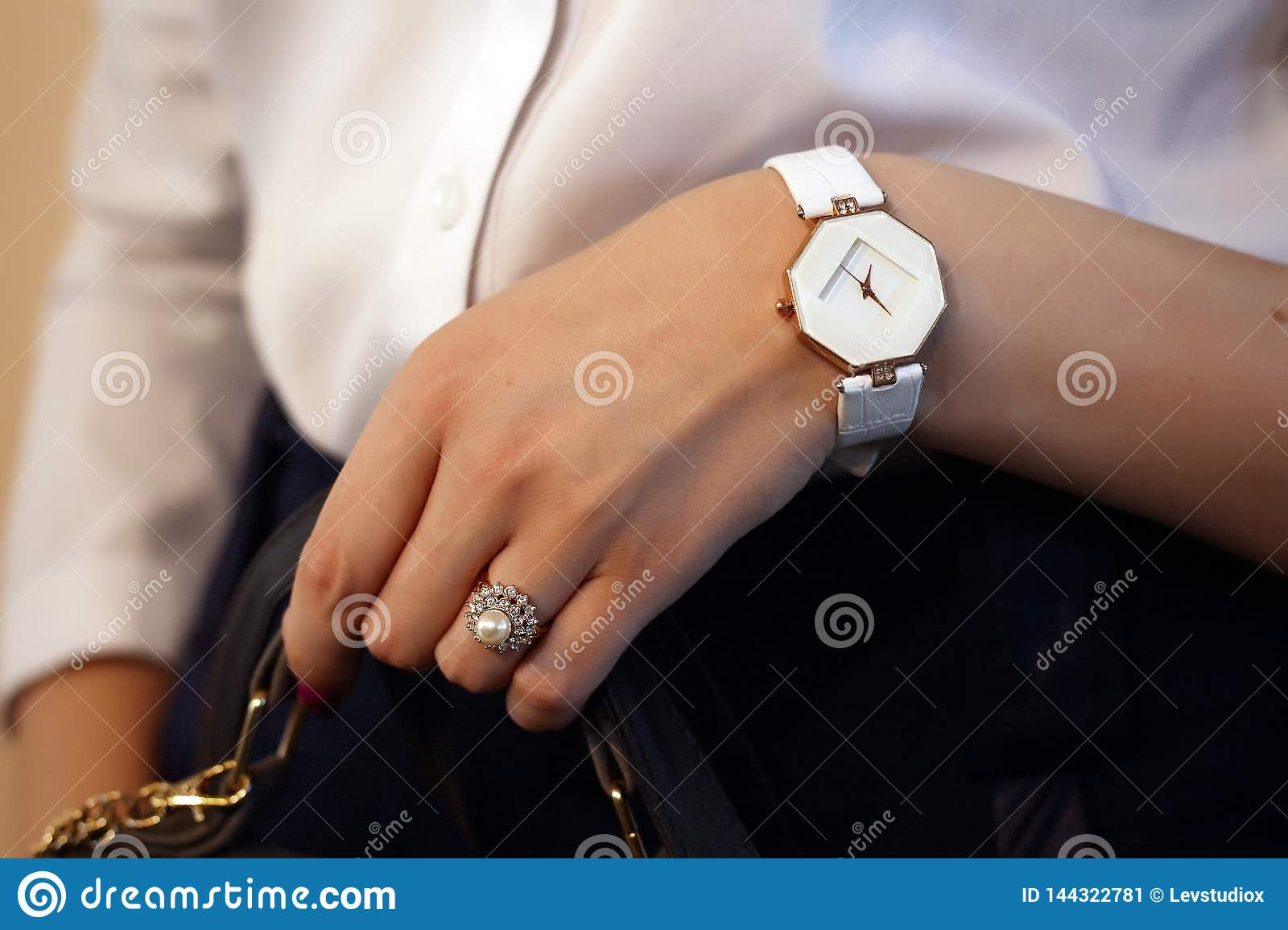 A ring with stones and a watch on the hand of a girl