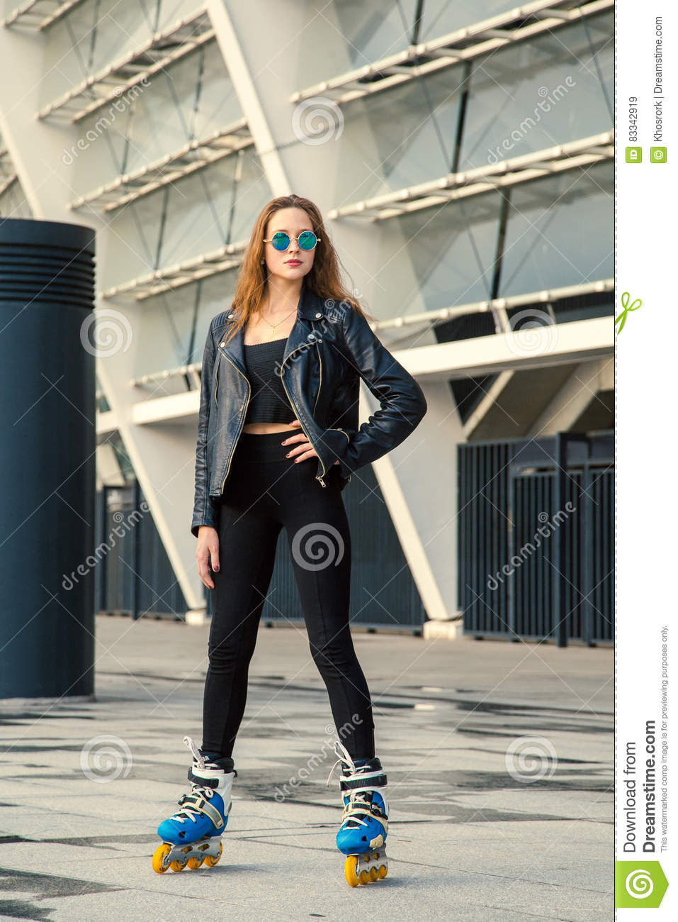 Girl on rollerblades standing in building background.