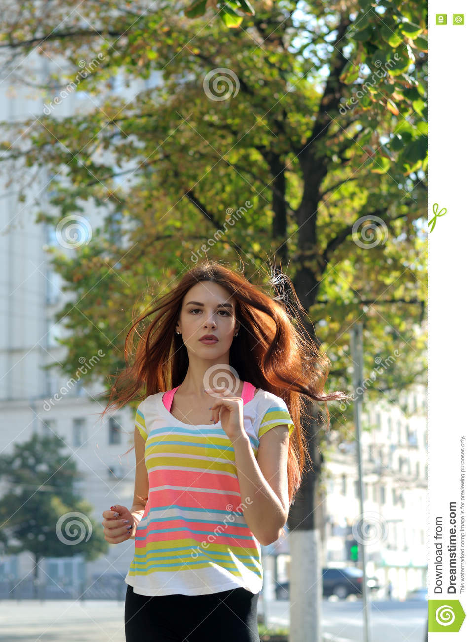 f72f190c Girl running down the street early in the morning in the city. She has long  red hair and wearing a striped shirt.