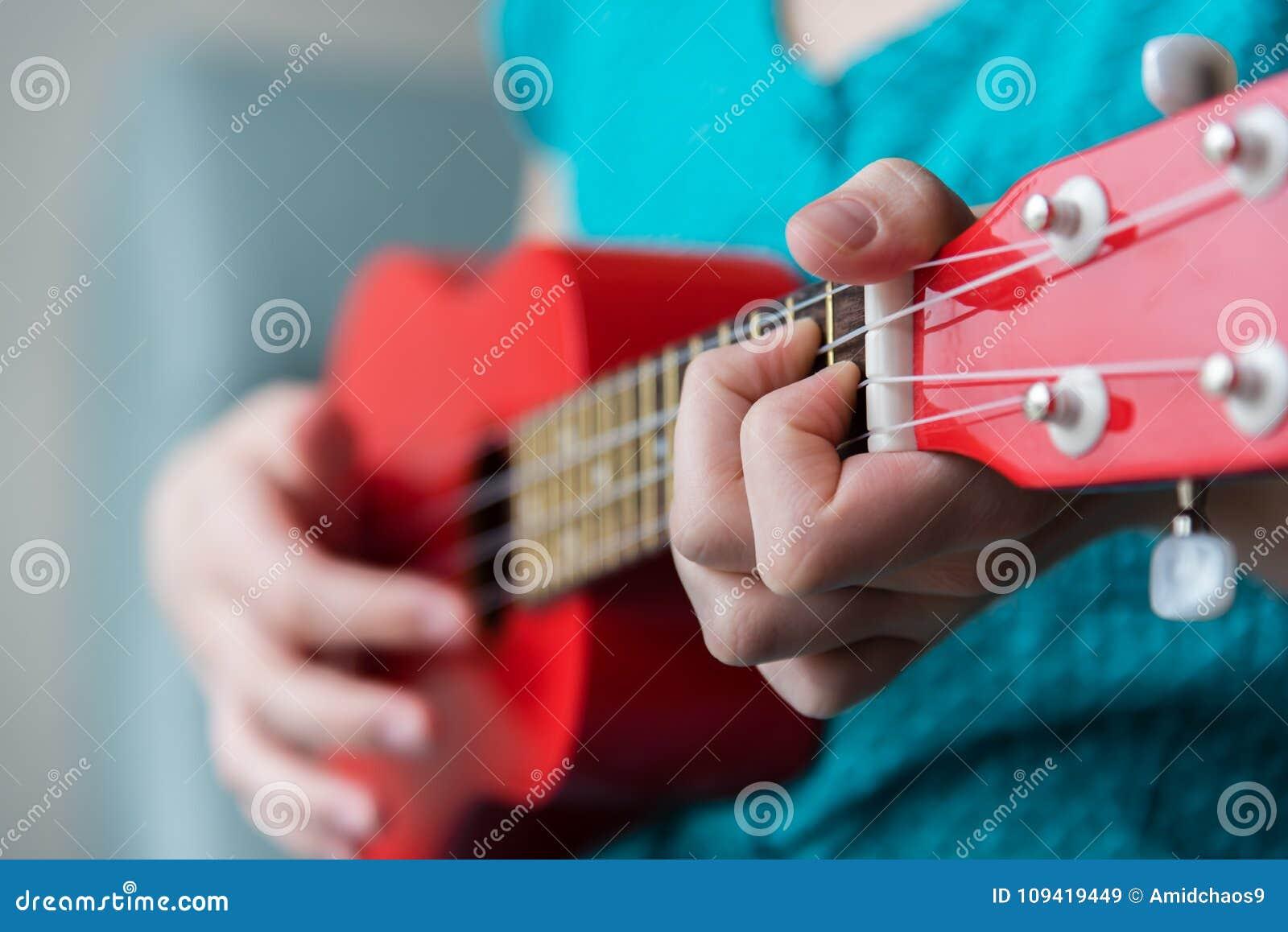 Girls Fingers Playing Chord On Fretboard Of Red Ukulele Stock Image