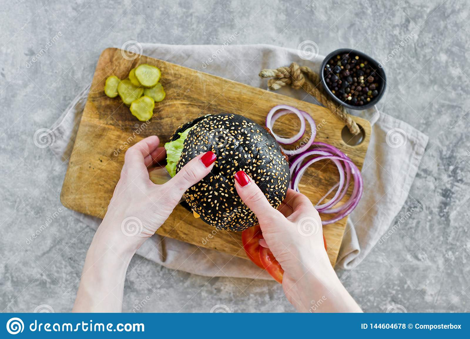 Girl`s hand holding a black Burger. Top view, gray background, space for text.