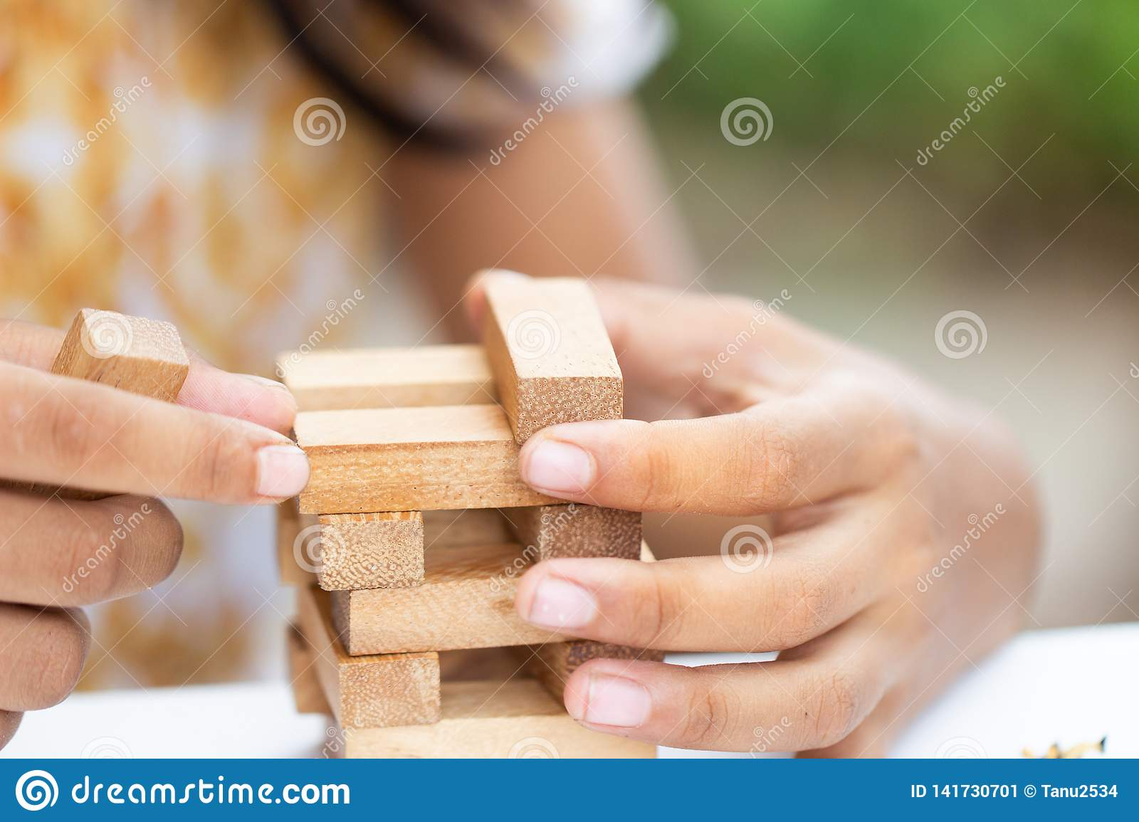 Girl`s hand holding playing wooden block,