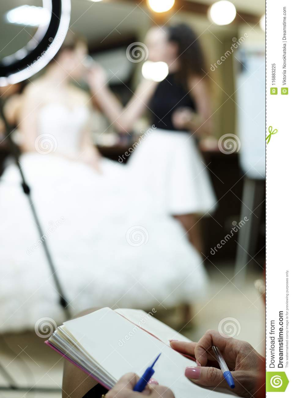 The girl`s hand holds a pen on sheet of paper.