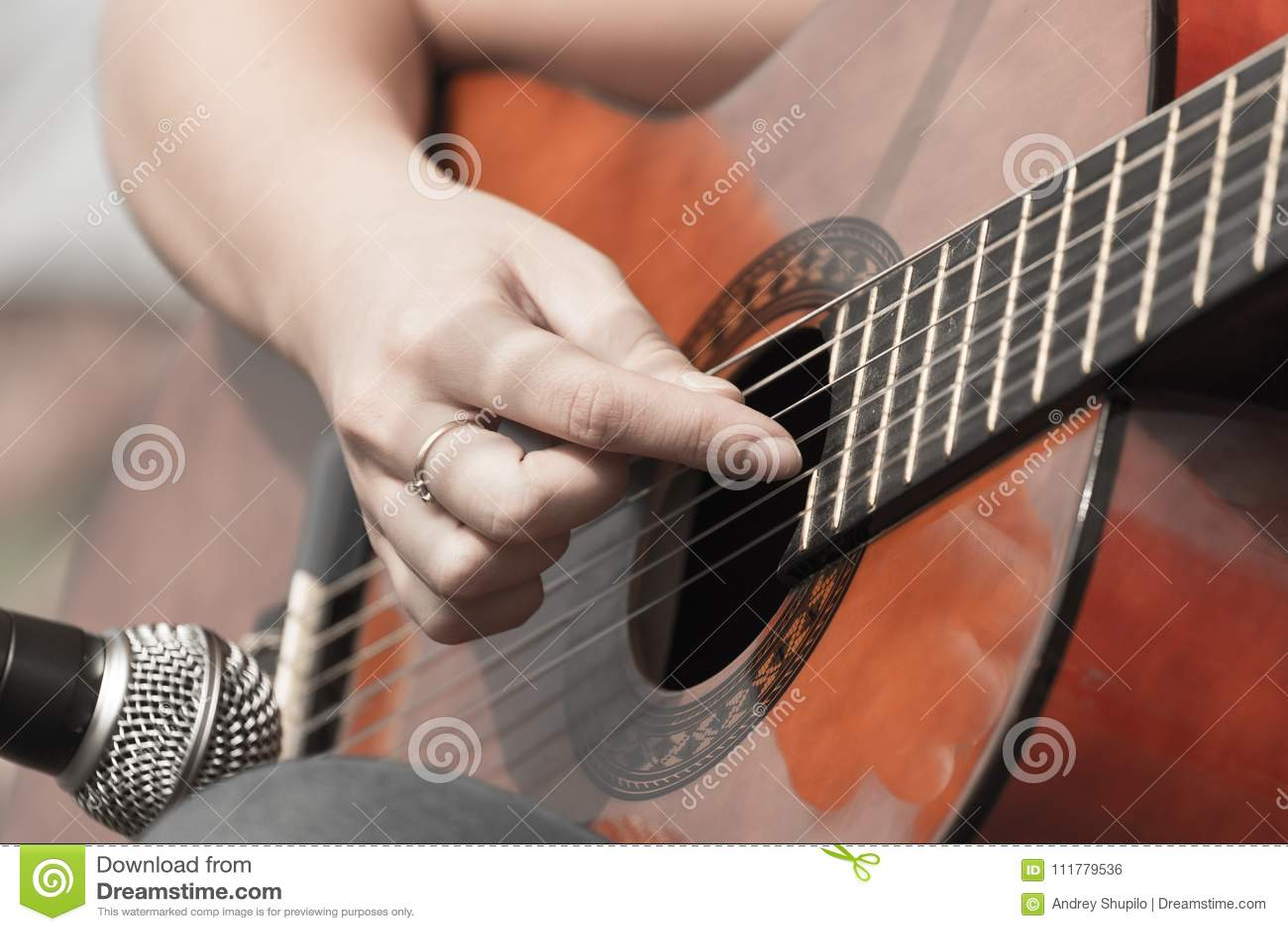 Girl`s hand playing guitar