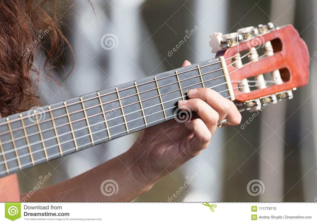 Girl`s hand playing guitar