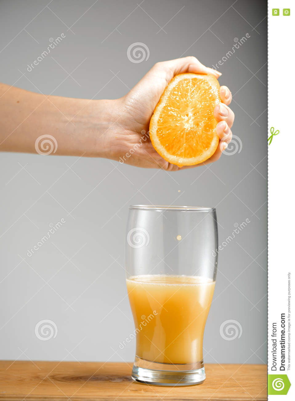 Girl s hand squeezing out juice from orange into glass.