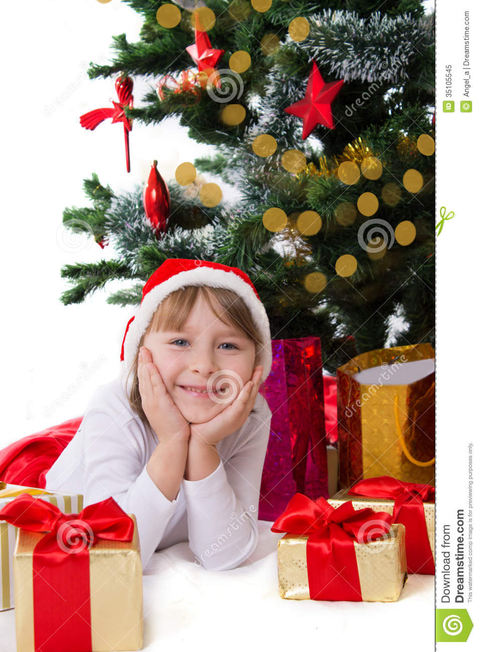 Girl in santa hat lying under christmas tree royalty free stock photo