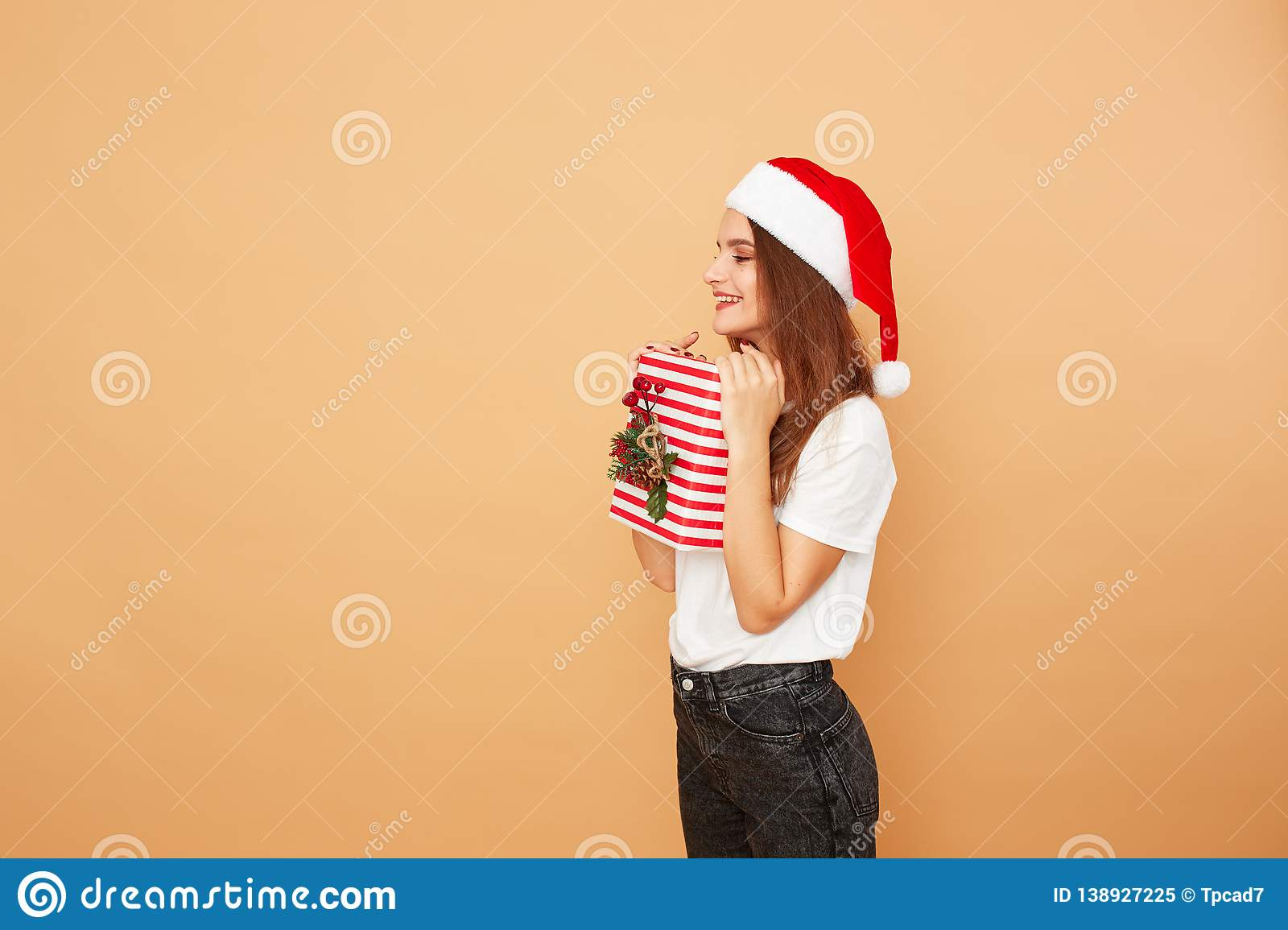 Girl in Santa`s hat dressed in white t-shirt and jeans holds a Christmas gift in her hands on the beige background in