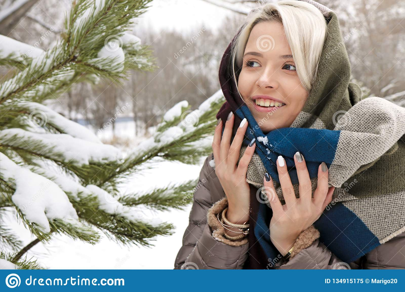 Girl in a scarf and a fashionable winter multi-colored manicure