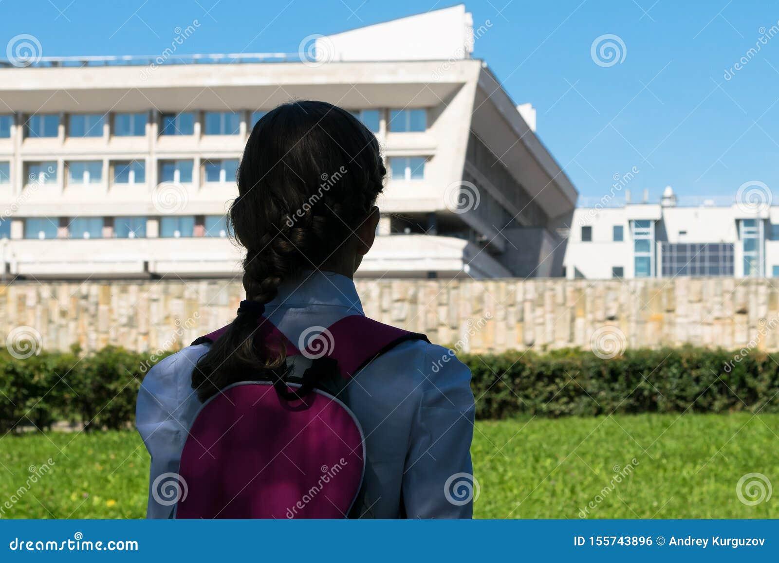 Girl in school uniform looking at the school building , rear view