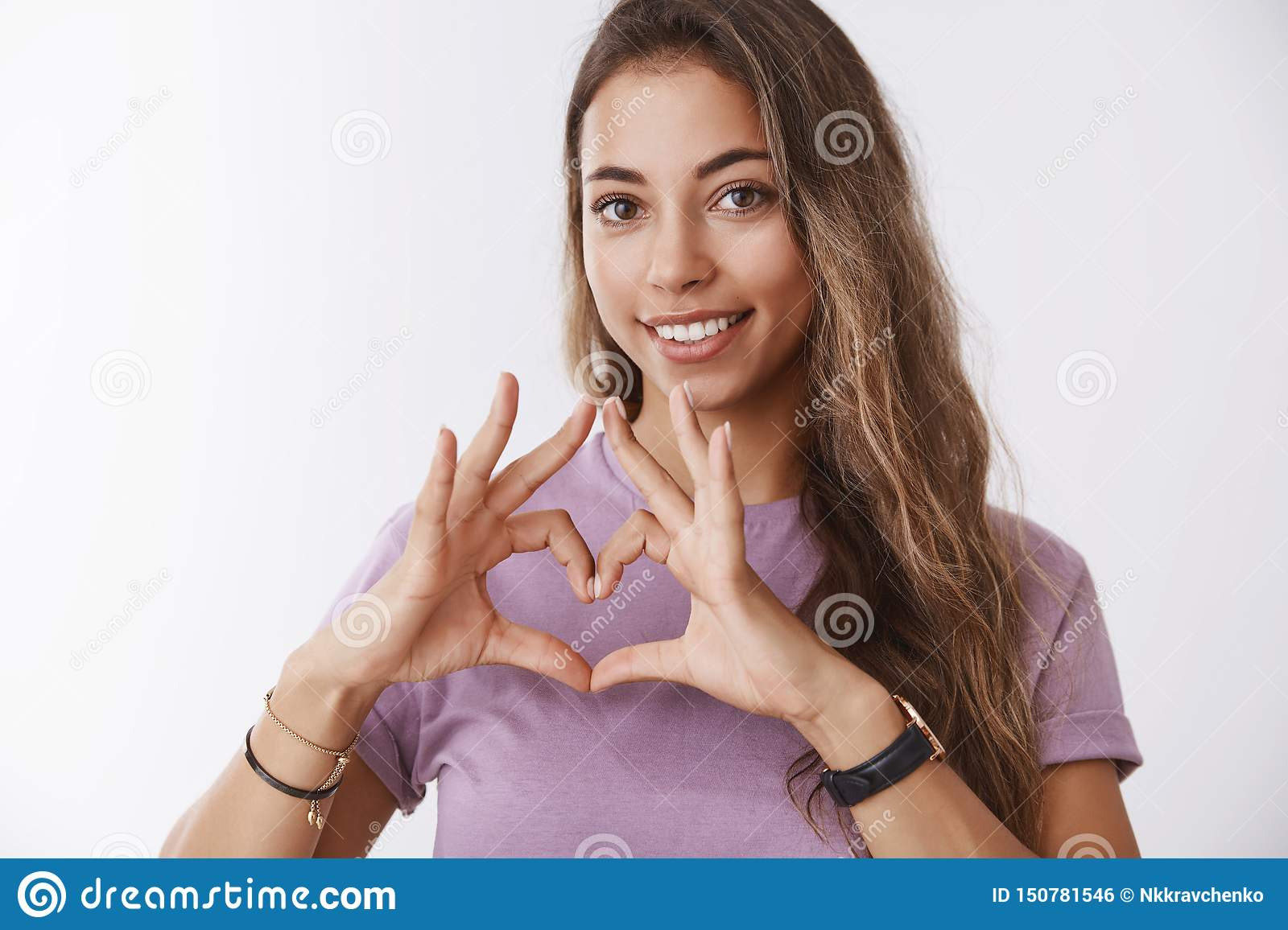 Girl searching key your heart. Attractive feminine tender tanned european woman curly hair, showing love gesture smiling