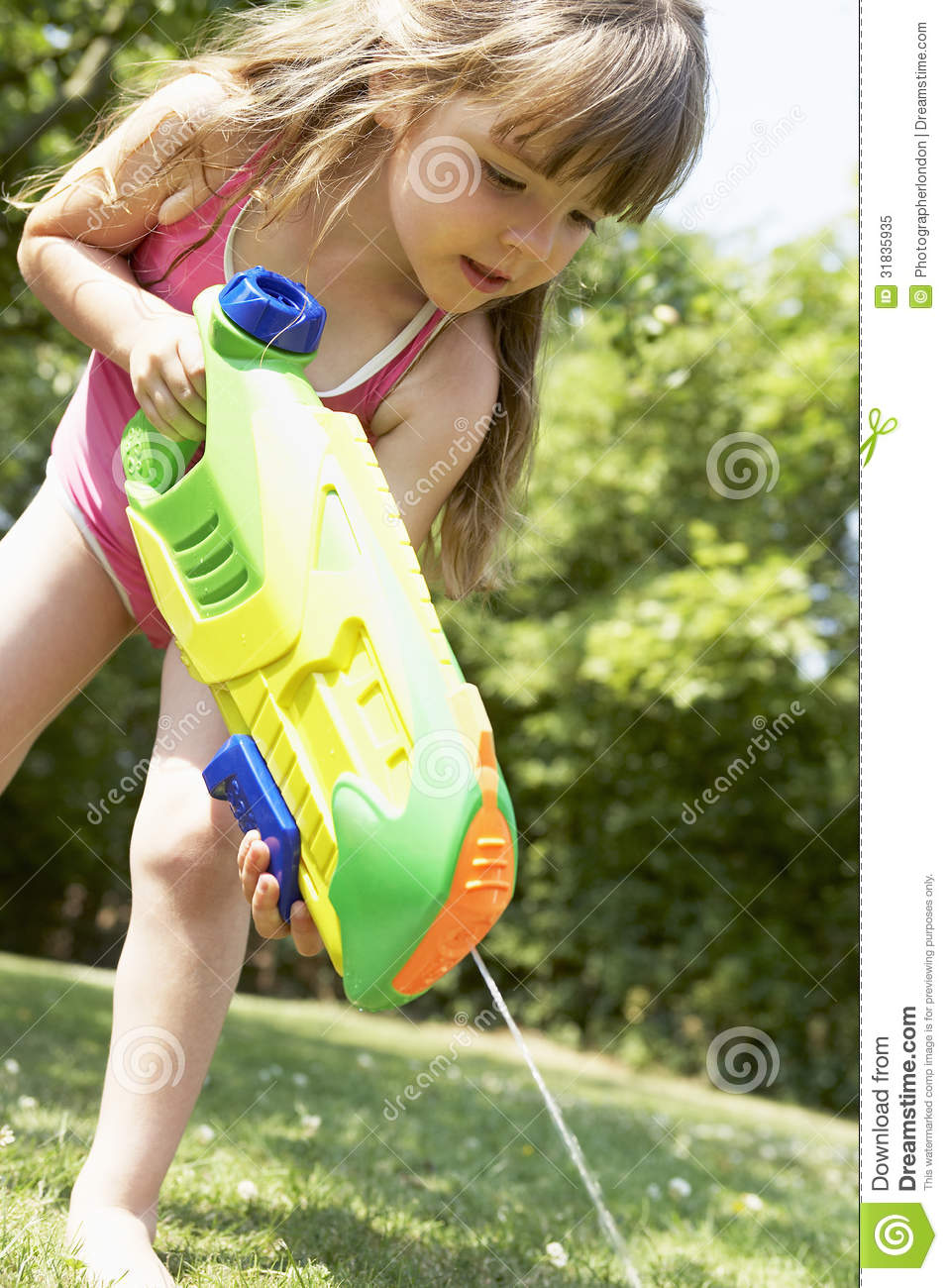 Girl Shooting Water Pistol Into The Grass Royalty Free