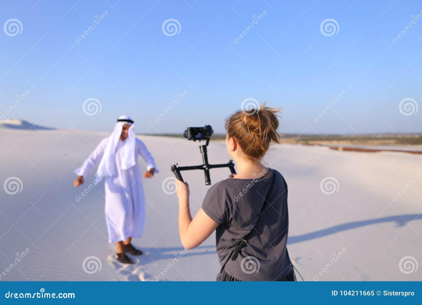 Girl shoots on camera dancing Muslim man in spacious desert on h