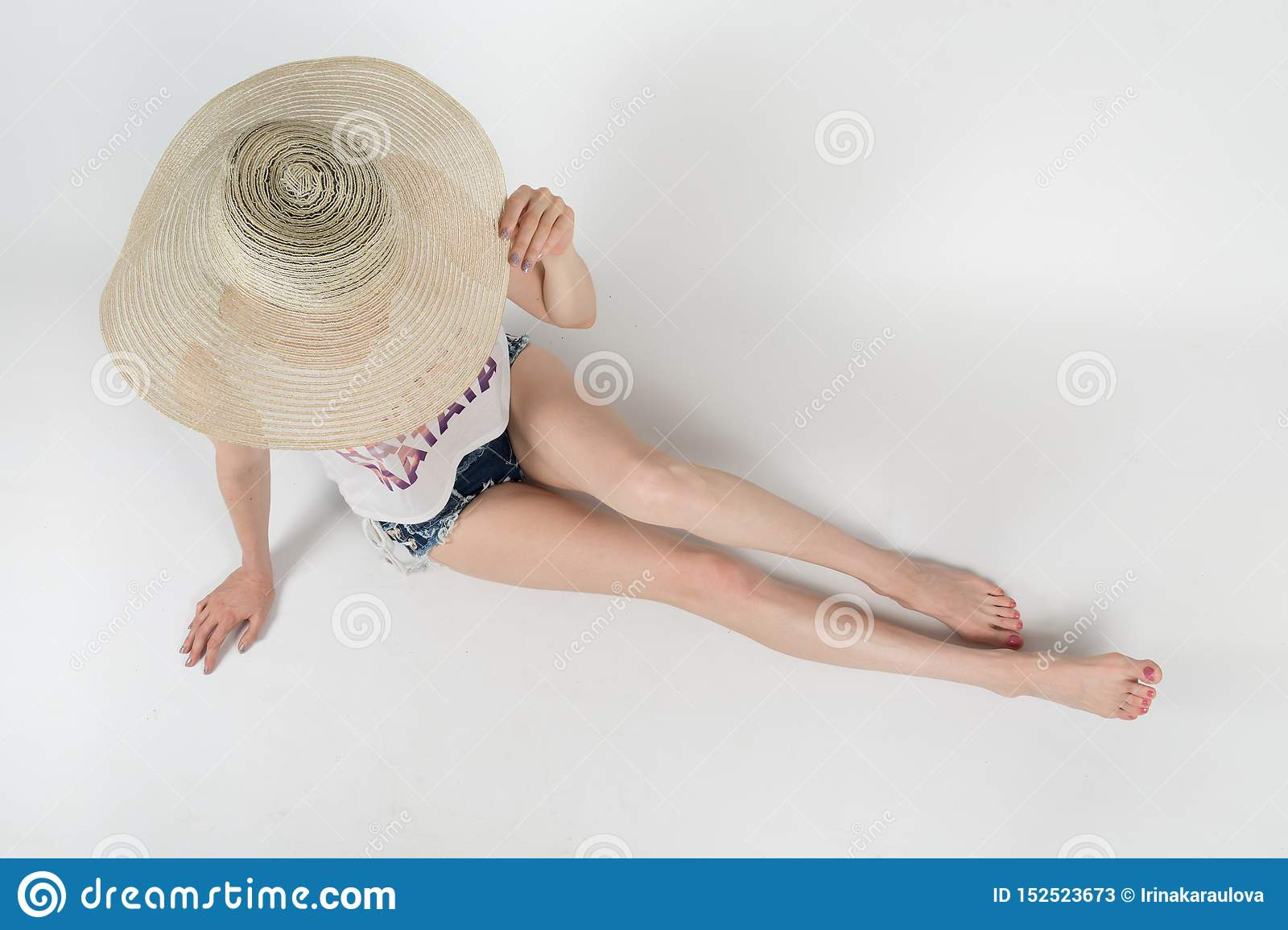 The girl in shorts and hat covering her face sitting on white background isolated