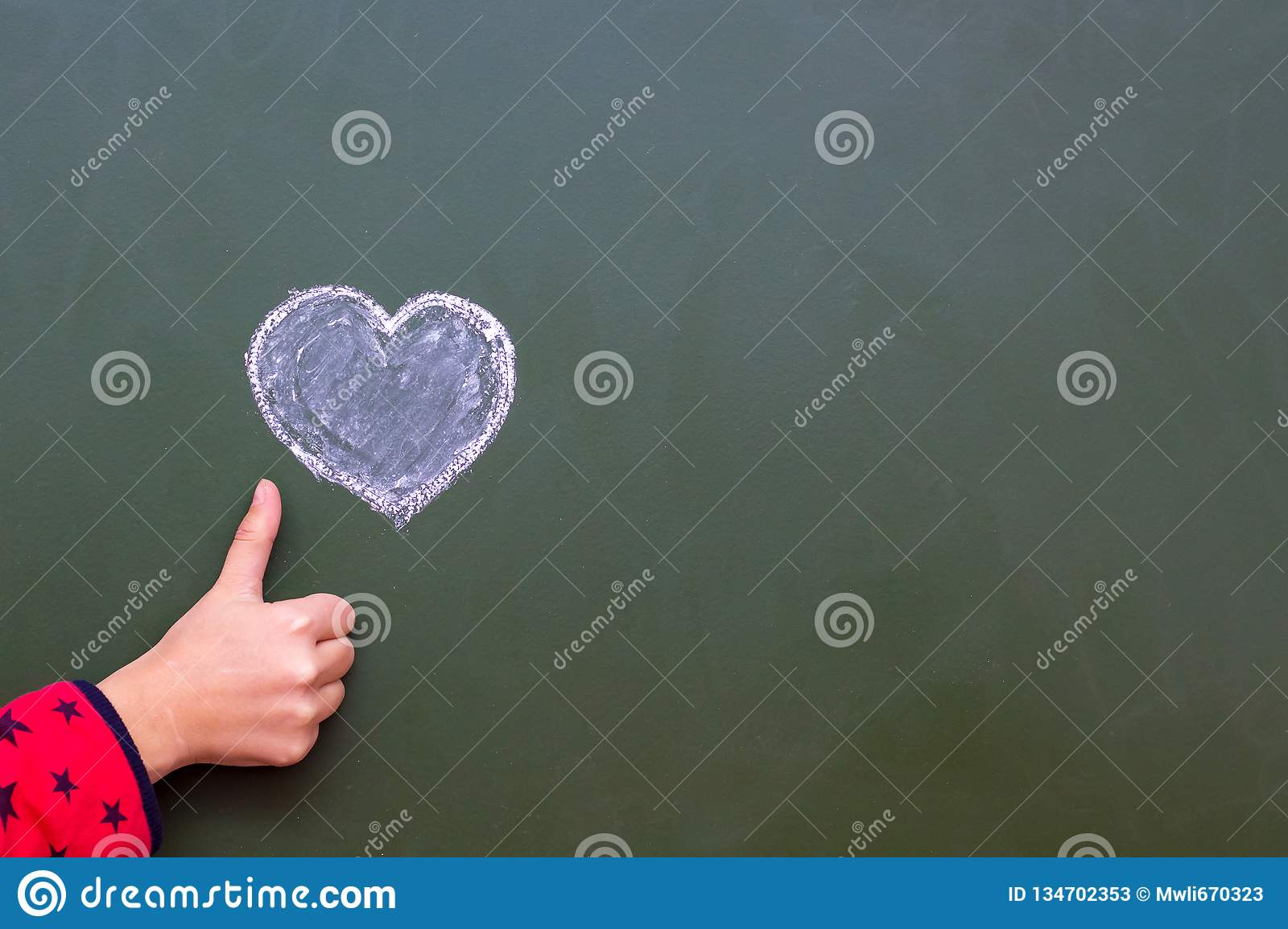 The girl shows by hand ok next to the heart drawn by the chalk on a blackboard. Congratulations on Valentine`s Day. Free space fo