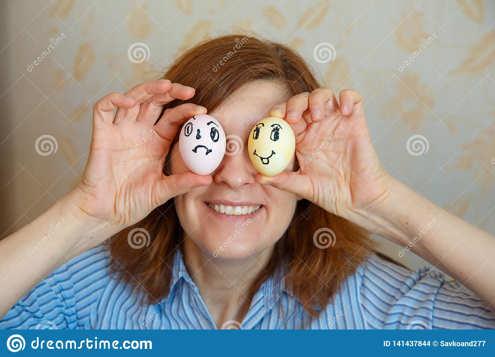 Girl shows painted eggs for Easter with funny faces