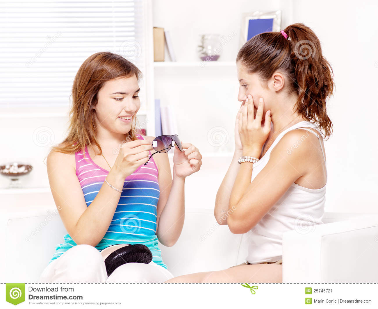Girl shows sunglasses to her friend