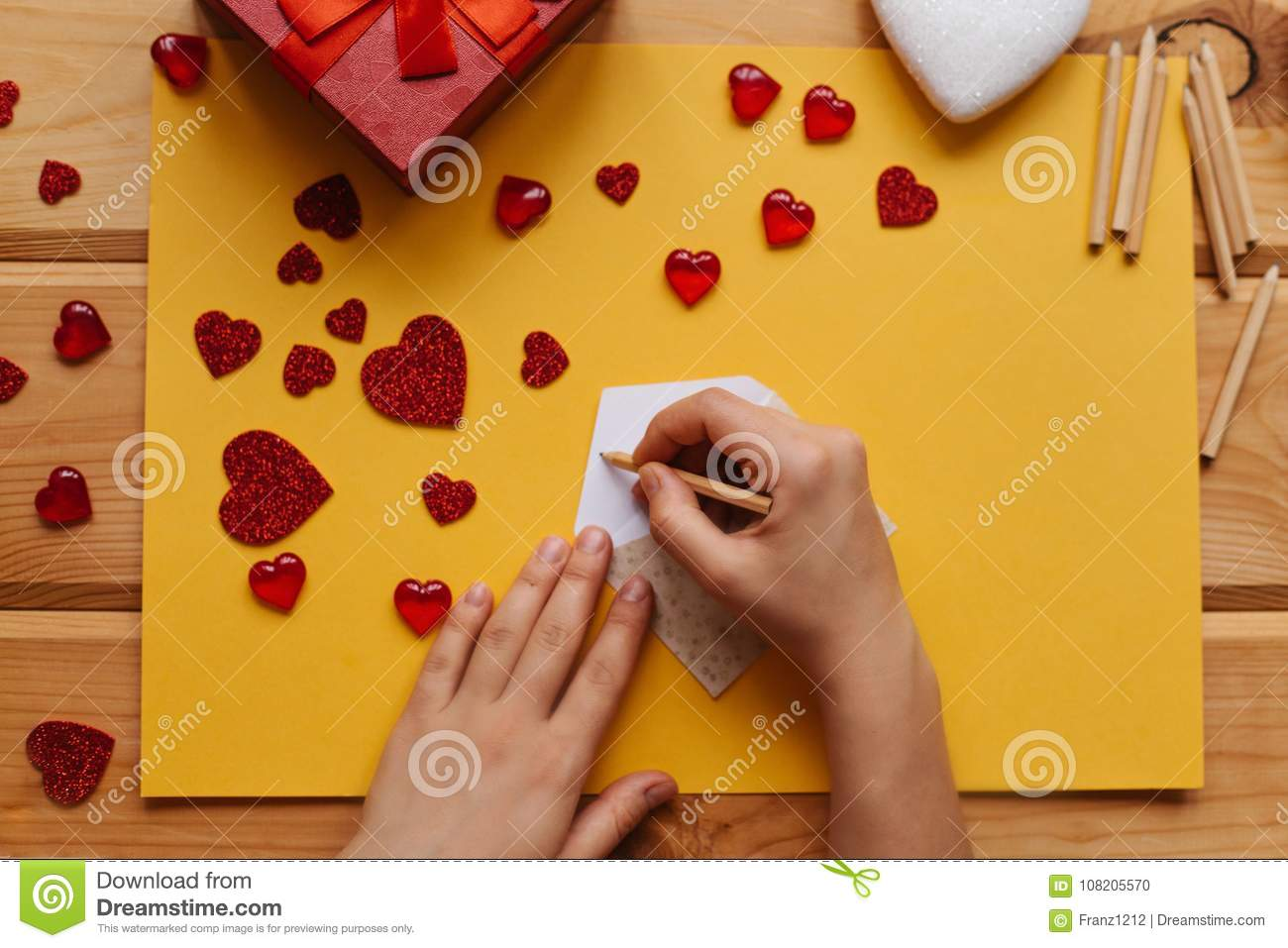 The girl signs an envelope with congratulations on the holiday to send it, beside on the wooden surface lie gifts