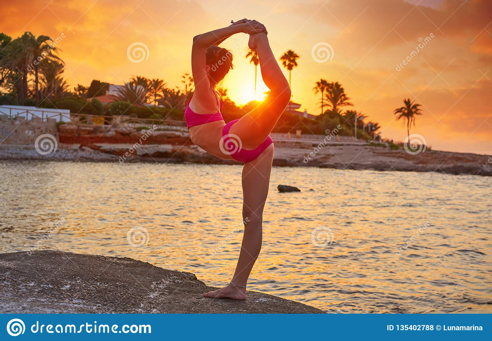 Girl silhouette at beach sunset gymnastics