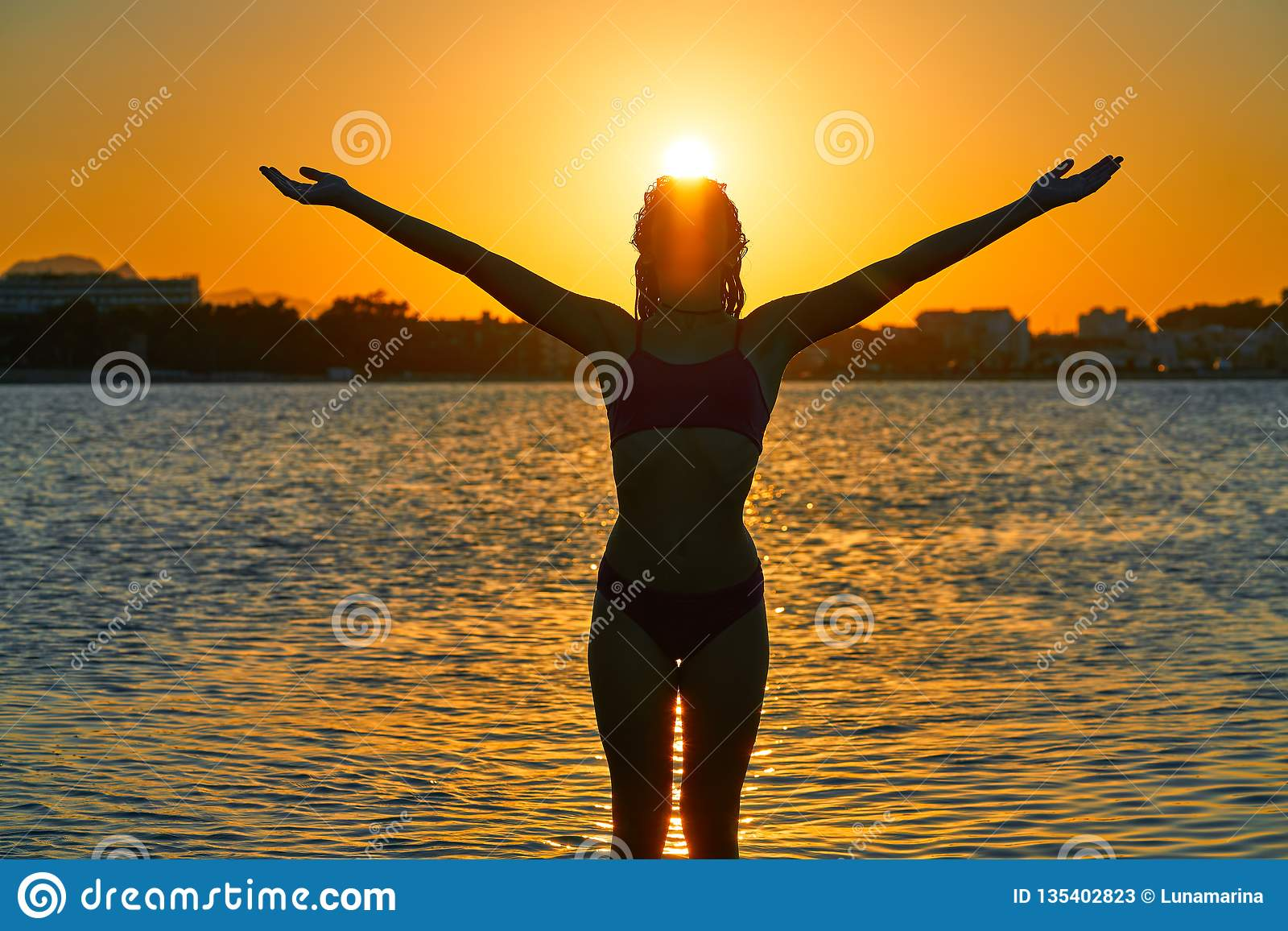 Girl silhouette at beach sunset open arms