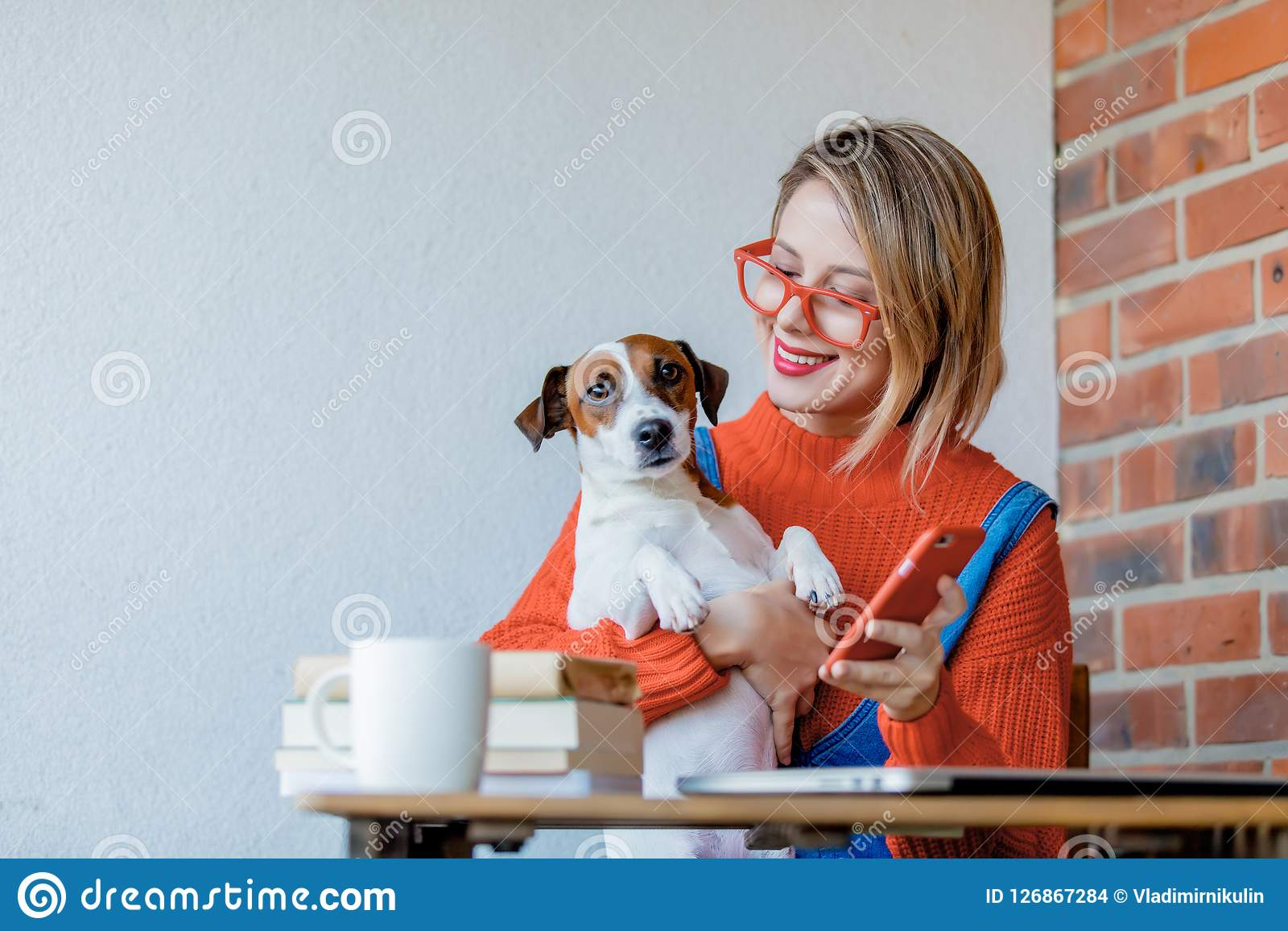 Girl sititng at table with computer and dog