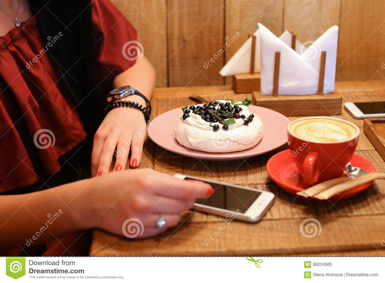 Girl sits and holds hands at table next to order of meringues, c