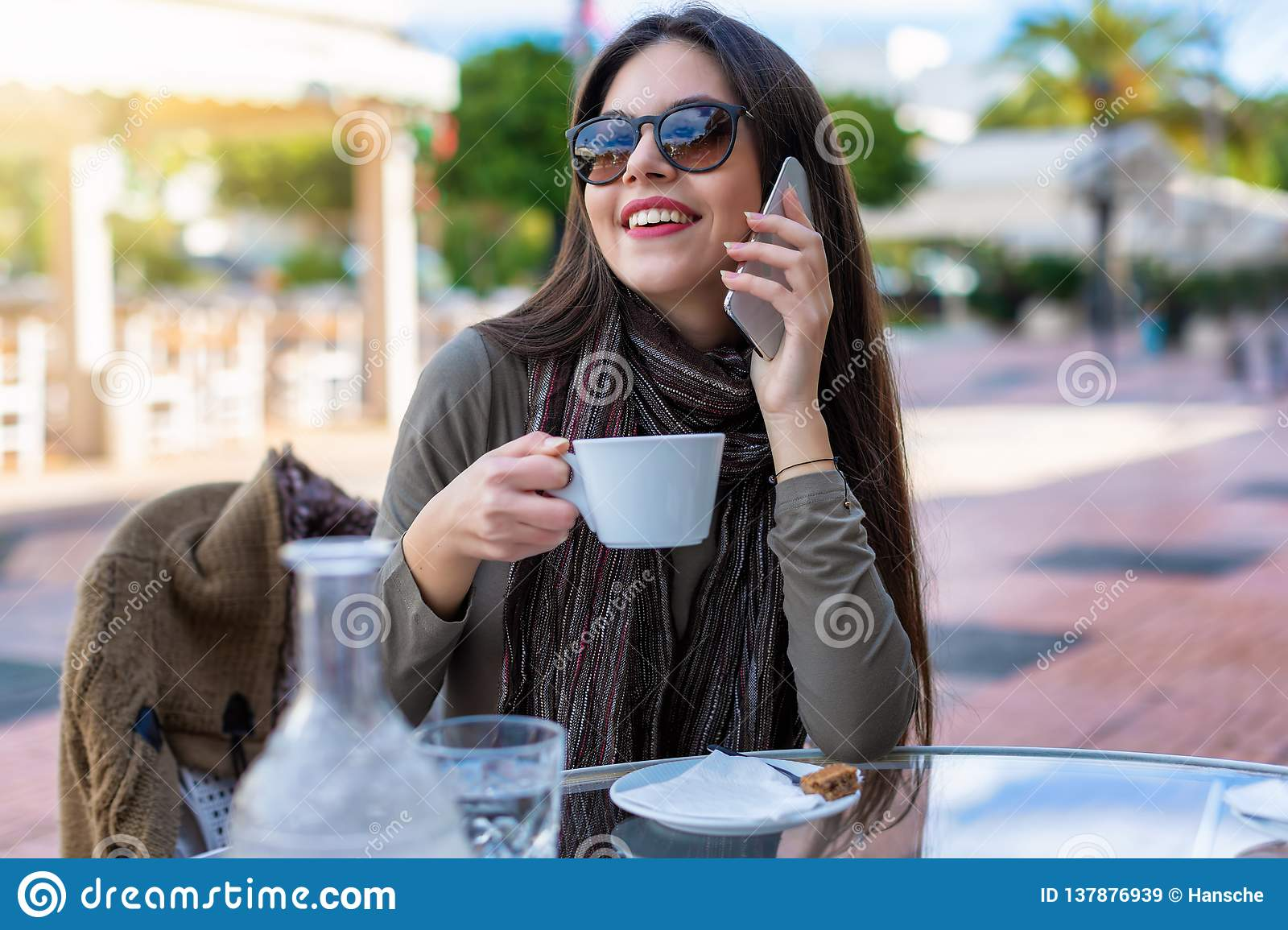 Girl sits outdoors in a cafe and talks to her mobile phone