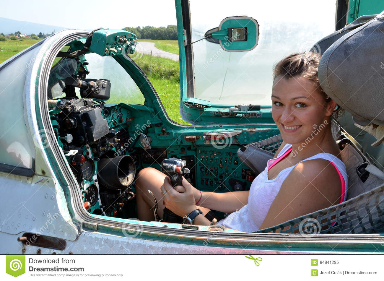 Girl Sits And Smiles In Cabin Of Old Jet Fighter MiG-21
