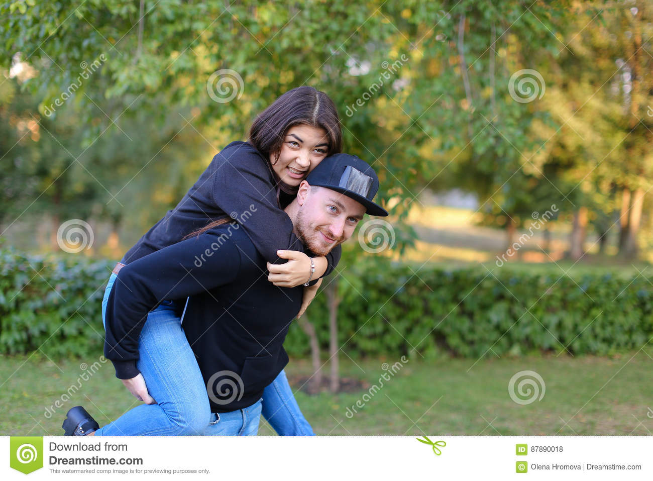 Girl sits on top of guy embracing neck, guy rolls lover both loo