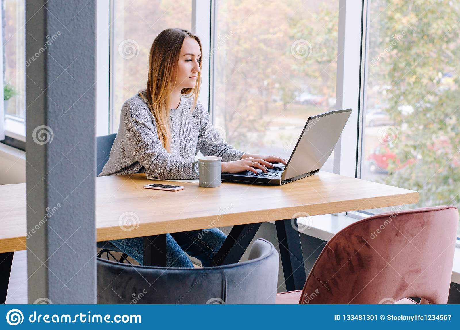 The girl sits working at the computer
