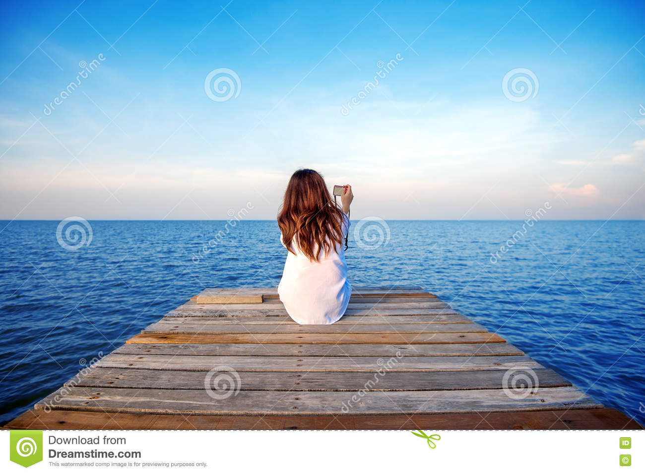 girl sitting alone and hand holding camera on a the wooden bridge