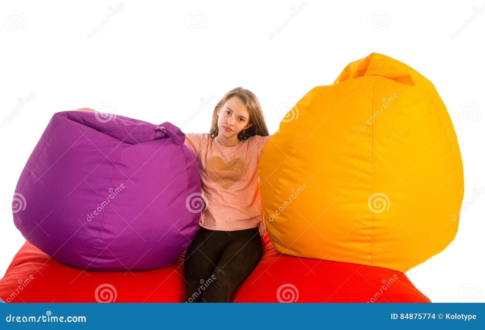 Girl Sitting Between Beanbag Chairs On Red Beanbag Sofa
