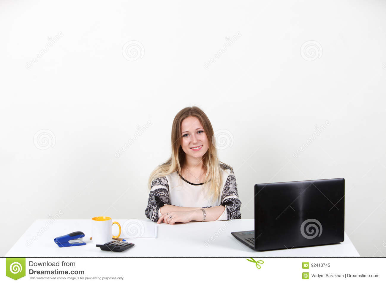 The girl sitting behind a desk in the Office. One on-white background.