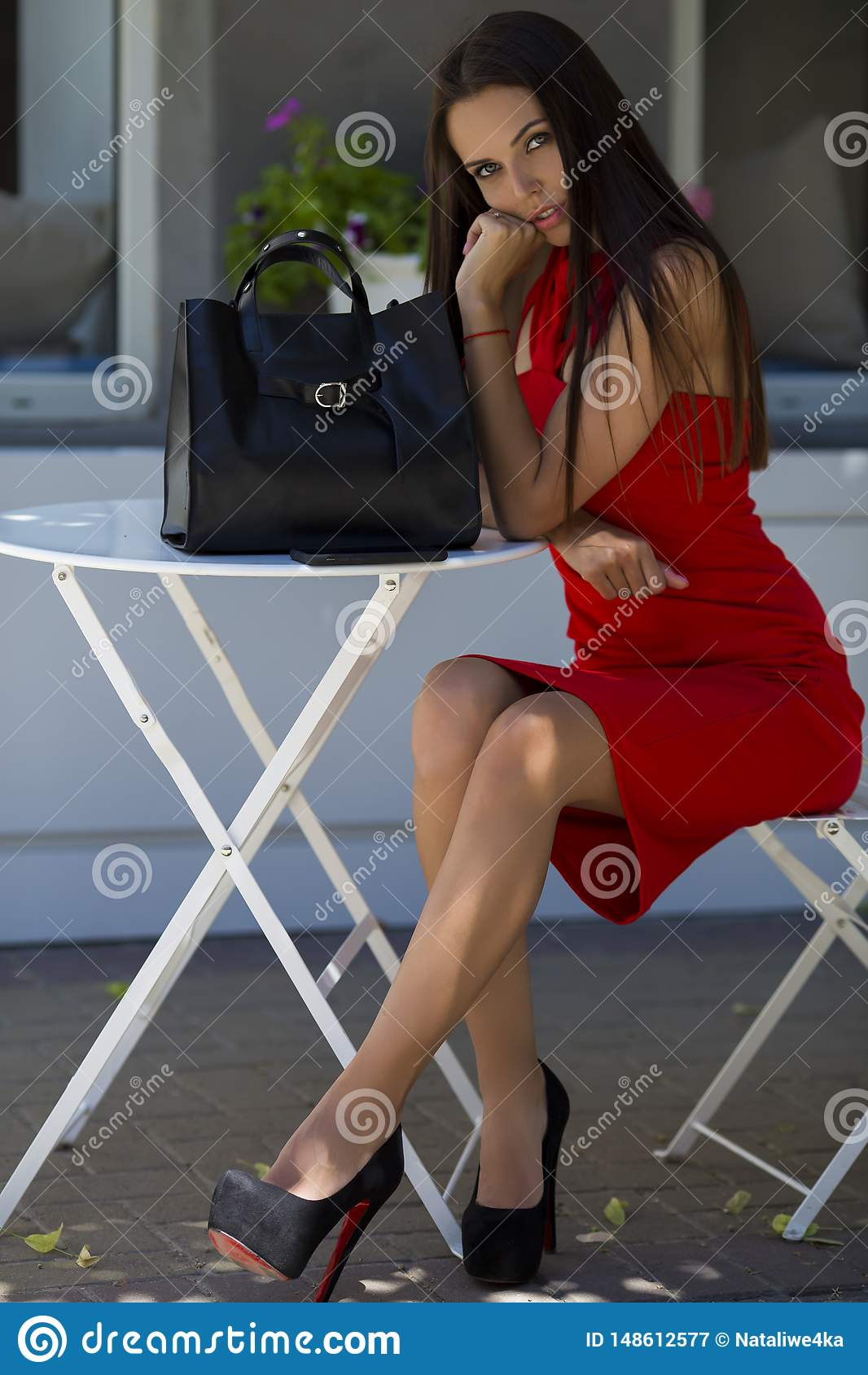girl sitting on the chair in chic shoes with a stylish black bag